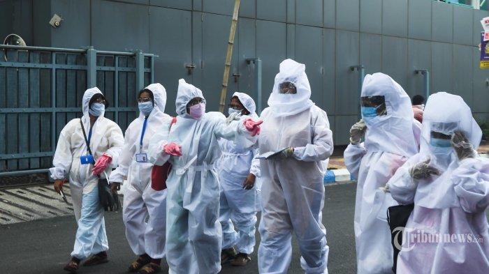 Pekerja kota yang mengenakan pakaian hazmat berjalan di daerah residensial untuk survei kesehatan dari pintu ke pintu rumah warga, selama penguncian nasional yang diberlakukan pemerintah sebagai tindakan pencegahan terhadap coronavirus COVID-19, di Kolkata. India. Rabu (29/4/2020). (AFP/Dibyangshu SARKAR)