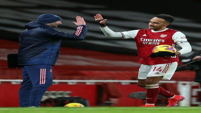 Striker Arsenal asal Gabon Pierre-Emerick Aubameyang (kanan) memegang bola pertandingan setelah mencetak hattrick pada pertandingan sepak bola Liga Utama Inggris antara Arsenal melawan Leeds United di Emirates Stadium di London pada 14 Februari 2021. Arsenal memenangkan pertandingan tersebut dengan skor 4-2.