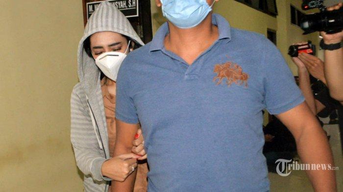Petugas Kepolisian menggiring artis FTV berinisial VS (jaket abu-abu) saat akan menjalani pemeriksaan di Mapolresta Bandar Lampung, Rabu (29/72020). Artis FTV berinisial VS tersebut diamankan oleh Unit Perlindungan Perempuan dan Anak (PPA) Satreskrim Polresta Bandar Lampung terkait dugaan kasus prostitusi online bersama dua mucikari berinisial I dan M. TRIBUN LAMPUNG/DENI SAPUTRA