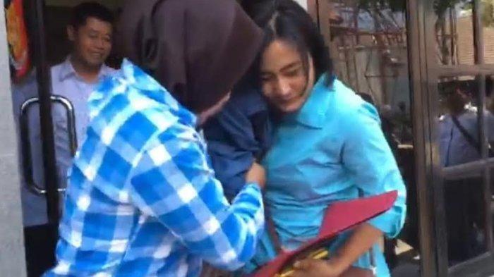 Penyidik Unit PPA Sat Reskrim Polresta Mojokerto melindungi bidan (tengah ditutupi kerudung biru) yang digerebek saat selingkuh bersama seorang dokter spesialis di Mojokerto, Selasa (1/10/2019). Penggerebekan itu dilakukan oleh polisi yang juga suami dari bidan tersebut.