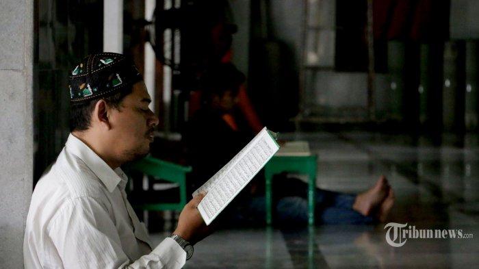 seorang umat muslim asik membaca Al Quran dalam suasana lenggang pada Bulan Ramadan di Masjid Kauman Semarang. Jawa Tengah, Minggu (26/4/2020).