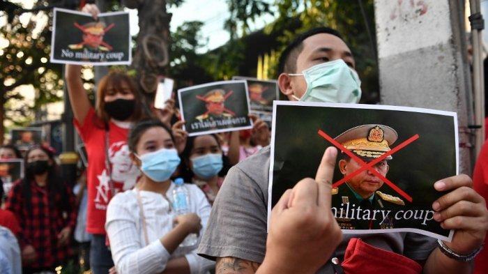 Seorang migran Myanmar memegang poster dengan gambar Kepala Jenderal Senior Min Aung Hlaing, panglima angkatan bersenjata Myanmar, saat mereka mengambil bagian dalam demonstrasi di luar kedutaan Myanmar di Bangkok pada 1 Februari 2021, setelah itu. Militer Myanmar menahan pemimpin de facto negara itu Aung San Suu Kyi dan presiden negara itu dalam kudeta.