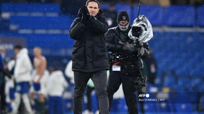 Seorang operator kamera televisi (kanan) bekerja saat pelatih kepala Chelsea Inggris Frank Lampard bertepuk tangan kepada para penggemar menyusul pertandingan sepak bola Grup E Liga Champions UEFA antara Chelsea dan FK Krasnodar di Stamford Bridge di London pada 8 Desember 2020. Pertandingan berakhir imbang di 1-1. Ben STANSALL / AFP