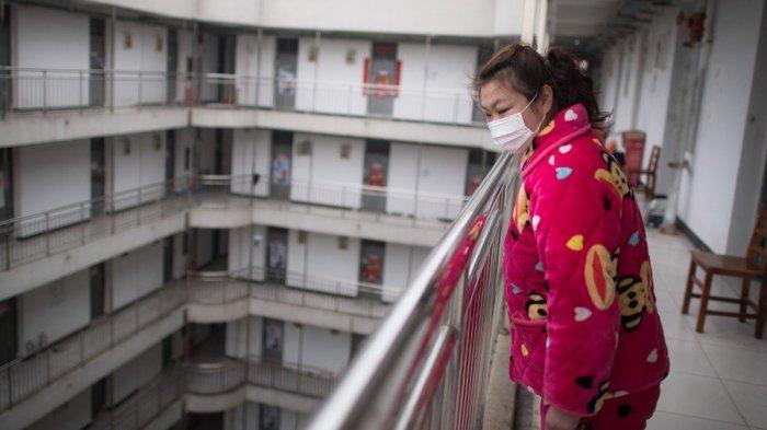 Seorang pasien coronavirus yang sudah pulih menunggu untuk meninggalkan pusat rehabilitasi di Wuhan, Cina tengah, setelah menyelesaikan karantina selama 14 hari di bawah pengawasan medis.