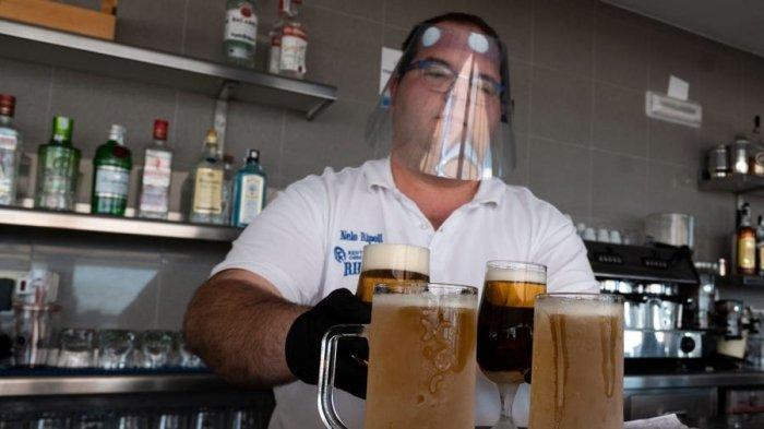 Seorang pelayan yang mengenakan face shield atau pelindung wajah mempersiapkan beberapa bir untuk disajikan di teras bar di pantai La Malvarrosa di Valencia, Spanyol pada 19 Mei 2020