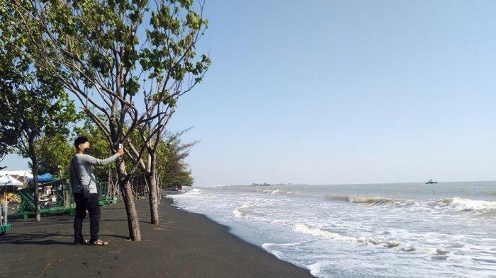 Seorang warga sedang mendokumentasikan suasana Pantai Ngebum, Kecamatan Kaliwungu, Kabupaten Kendal yang masih sepi lantaran masih ditutup, Rabu (17/6/2020).