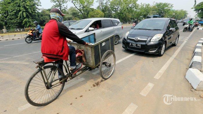 Pengendara sepeda terhalang lajunya oleh mobil yang parkir di Jalur Sepeda Jalan Pemuda, Rawamangun, Jakarta Timur, Senin (25/11/2019). Sejatinya mulai hari ini Polisi memberlakukan penilangan apabila pengendara melintasi jalur sepeda dengan dijerat Pasal 284 tentang Hak Utama Pejalan Kaki dan Pasal 287 Ayat 1 tentang Pelanggaran Rambu atau Marka Jalan dalam Undang-Undang Nomor 22 Tahun 2009.  Warta Kota/Alex Suban