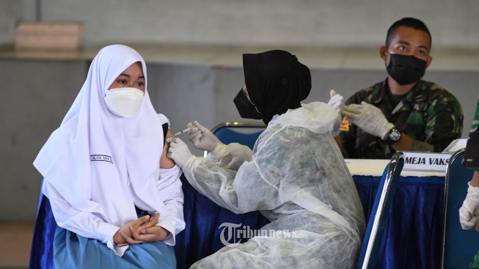 VAKSINASI PELAJAR - Petugas kesehatan melakukan vaksinasi COVID-19 kepada pelajar dalam Serbuan Vaksinasi COVID-19 di GOR Bola Basket AAL Bumimoro, Rabu (21/7/2021). Komando Pembinaan Doktrin Pendidikan dan Latihan TNI Angkatan Laut (Kodiklatal) melaksanakan vaksinasi COVID-19 yang diperuntukkan untuk anak usia 12 - 17 tahun guna mewujudkan kekebalan komunal atau 'herd immunity' menuju Indonesia sehat. SURYA/AHMAD ZAIMUL HAQ