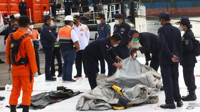 Petugas memeriksa benda yang diduga serpihan dari pesawat Sriwijaya Air SJ 182 rute Jakarta - Pontianak yang hilang kontak di perairan Pulau Seribu, di Dermaga JICT, Jakarta, Minggu (10/1/2021). Pesawat Sriwijaya Air SJ 182 yang hilang kontak pada Sabtu (9/1) sekitar pukul 14.40 WIB di ketinggian 10 ribu kaki tersebut membawa enam awak dan 56 penumpang.
