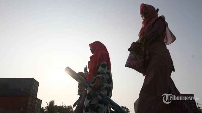 Warga menuju ke tempat sholat Idul Fitri di kawasan Pelabuhan Sunda Kelapa, Jakarta, Jumat (15/6/2018). Sesuai ketetepan pemerintah 1 Syawal 1439 Hijriyah jatuh pada hari ini. Meski salat di kawasan galangan kapal laut, namun jamaah tetap khusyuk menjalankannya.