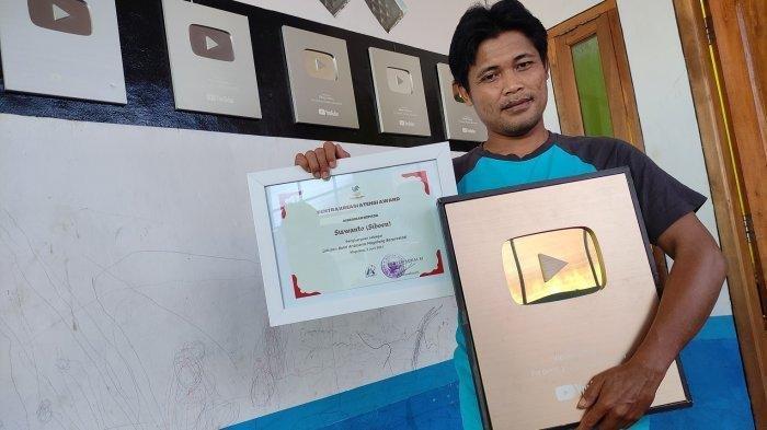 Siboen yang bernama asli Siswanto (37) saat menunjukan gold button dari YouTube dan penghargaan dari Menteri Sosial RI, Tris Risma harini, di rumahnya di Desa Kasegeran, Kecamatan Cilongok, Banyumas, pada Rabu (9/6/2021).