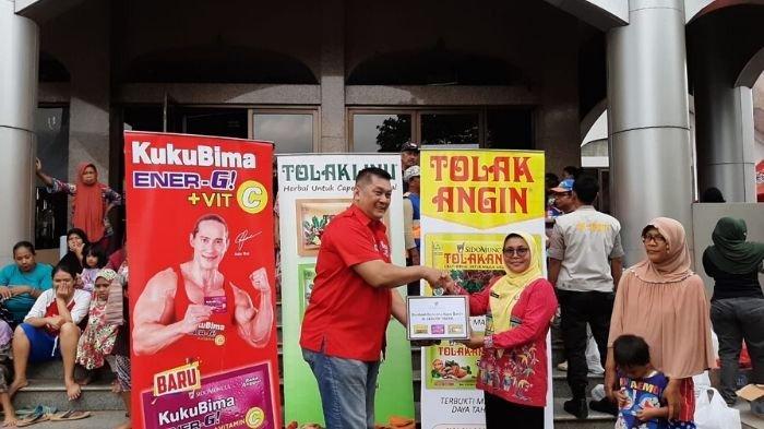 Brand Ambassador Kuku Bima Energi, Donny Kesuma menyerahkan bantuan dari PT Industri Jamu dan Farmasi Sido Muncul Tbk  kepada Kepala Seksi Kesejahteraan Masyarakat Cipinang Melayu, Sus Haryati di Posko Universitas Borobudur Jakarta, pada Kamis (2/1/2019) siang. Tribunnews/Dea Duta Aulia