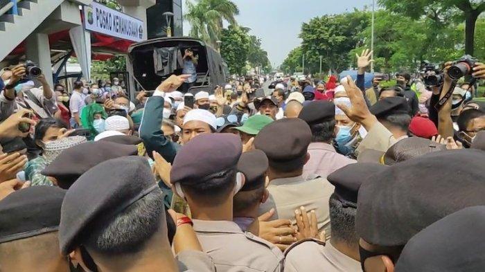 Terjadi aksi saling dorong antar simpatisan Habib Rizieq Shihab (HRS) dengan aparat kepolisian di depan Pengadilan Negeri Jakarta Timur, pada Jumat (26/3/2021).
