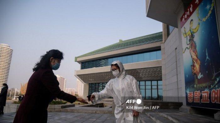 Seorang penonton menjalani pemeriksaan kesehatan sebagai bagian dari tindakan pencegahan terhadap virus corona Covid-19, sebelum pertunjukan oleh Rombongan Akrobatik Nasional Korea Utara di Teater Sirkus Pyongyang pada 16 November 2020.