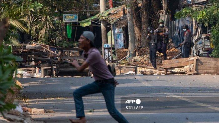 Situasi Myanmar. Seorang pengunjuk rasa berlari sebagai pasukan keamanan (atas L) mengarahkan senjata selama demonstrasi menentang kudeta militer di Mandalay pada 2 Maret 2021.
