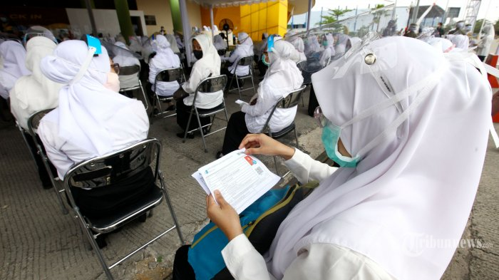 Peserta Seleksi Kompetisi Bidang (SKB) pada Seleksi CPNS Kota Bandung Formasi Tahun 2019 melewati tahapan penerapan dan pemeriksaan protokol kesehatan Covid-19 sebelum masuk ruang tes, di Gedung Youth Sport Center Jabar Arcamanik, Jalan Pacuan Kuda, Kota Bandung, Jawa Barat, Senin (14/9/2020). Sebanyak lebih kurang 1.400 peserta mengikuti SKB CPNS Kota Bandung Formasi Tahun 2019 yang dibagi dalam enam sesi selama dua hari dengan menerapkan protokol kesehatan ketat sebelum masuk ruang tes, yakni setiap peserta wajib cuci tangan, mengenakan masker dan pelindung wajah, diperiksa suhu tubuh, menjaga jarak aman dengan peserta lain, pakai sarung tangan, membersihkan tangan dengan handsanitizer, dan diperiksa metal detektor. Tribun Jabar/Gani Kurniawan