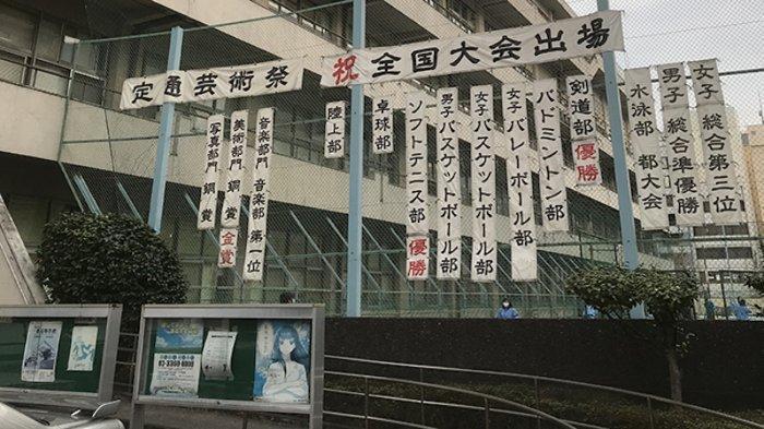 Sebuah SMA Negeri Tokyo dengan berbagai pengumuman kegiatannya di lapangan olahraga mereka
