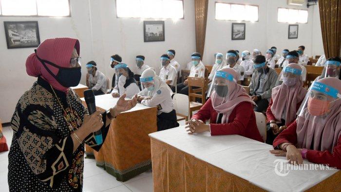 Kepala Sekolah SMK PGRI 13 Surabaya, Sri Wiludjeng memberi paparan sebelum simulasi belajar-mengajar pada era new normal yang digelar pihak sekolah, di Kota Surabaya, Jawa Timur, Rabu (17/6/2020). Simulasi digelar agar siswa paham dan tahu proses belajar-mengajar saat new normal dan nanti saat diperbolehkan belajar-mengajar secara tatap muka. Proses belajar-mengajar secara tatap muka saat new normal memperhatikan dengan ketat protokol kesehatan, di antaranya harus cuci tangan, penggunaan hand sanitizer, dan diperiksa suhu tubuhnya sebelum masuk kelas, serta penggunaan face shield (pelindung wajah) baik untuk siswa maupun guru. Surya/Ahmad Zaimul Haq