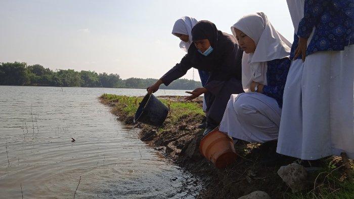 Siswa-siswi SMP Muhammadiyah 5 Tanon (SMP Militan), Kabupaten Sragen, Jawa Tengah, merayakan kelulusan dengan cara membersihkan area wisata Waduk Ketro di Kecamatan Tanon dan menebar benih ikan pada Jumat (4/6/2021). (istimewa)