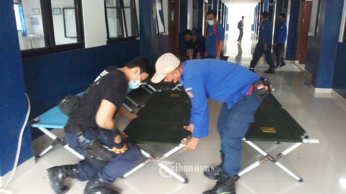 RUANG ISOLASI BARU - Pekerja sedang mempersiapkan sarana dan prasarana ruang isolasi terkonsentrasi baru bagi pasien Covid-19, yang menempati gedung SMP Negeri 30, Kota Tangerang, Senin (21/6/2021). Masih tingginya angka penyebaran Covid-19 di Kota Tangerang, membuat pihak Pemkot Tangerang menambah ruang isolasi baru sebagai langkah antisipasi. WARTA KOTA/NUR ICHSAN
