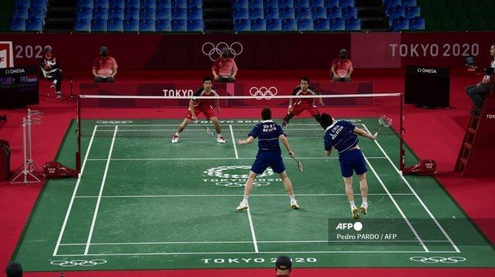 Soh Wooi Yik (tengah) dari Malaysia terlihat di samping Aaron Chia dari Malaysia dalam pertandingan medali perunggu bulu tangkis ganda putra melawan Mohammad Ahsan dari Indonesia (atas kanan) dan Hendra Setiawan dari Indonesia selama Olimpiade Tokyo 2020 di Musashino Forest Sports Plaza di Tokyo pada Juli 31, 2021.