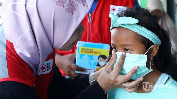 Anggota PMI memberikan sosialisasi tentang virus Corona kepada warga di Kota Tua Penagi, Natuna, Kepulauan Riau, Kamis (6/2/2020). Sosialisasi dan pembagian masker tersebut untuk memberi pemahaman kepada warga yang berada sekitar satu kilometer dari tempat diobservasinya 238 WNI pascaevakuasi dari Wuhan, Hubei, China yang memasuki hari kelima dalam keadaan sehat dan baik. TRIBUNNEWS/IRWAN RISMAWAN (TRIBUNNEWS/IRWAN RISMAWAN)