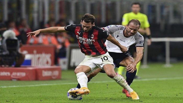 Gelandang AC Milan Hakan Calhanoglu (kiri) menantang bek Italia Bologna Lorenzo De Silvestri dalam pertandinganSerie A Italia AC Milan vs Bologna di stadion San Siro di Milan pada 21 September 2020.