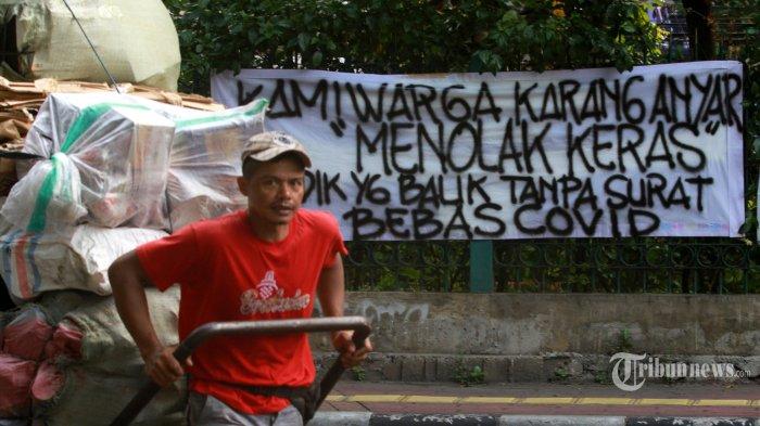 Spanduk peringatan untuk pemudik dipasang oleh warga di kawasan Sawah Besar, Jakarta Pusat, Minggu (16/5/2021). Spanduk yang ditulis dengan cat semprot tersebut untuk memperingatkan warga yang kembali dari mudik agar membawa surat bebas Covid-19. Warta Kota/Henry Lopulalan