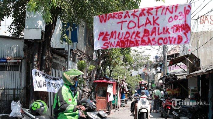 Warga melintas di dekat spanduk peringatan untuk pemudik yang kembali ke Jakarta di kawasan Sawah Besar, Jakarta Pusat, Minggu (16/5/2021). Spanduk tersebut untuk memperingati warga yang kembali dari mudik agar membawa surat bebas Covid-19. Tribunnews/Irwan Rismawan