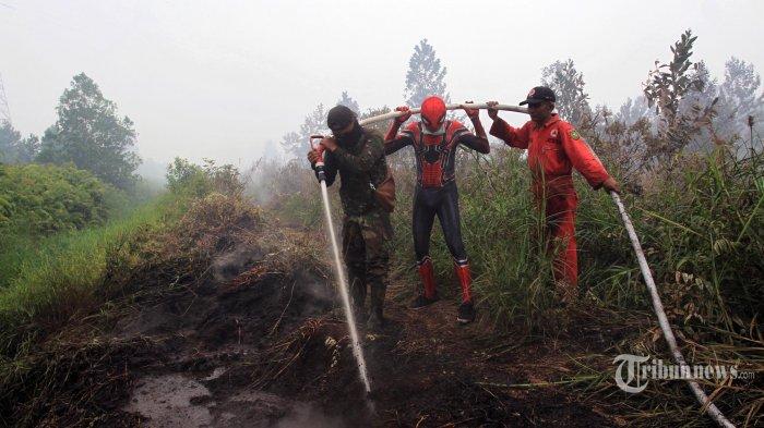 Warga yang menggunakan kostum pahlawan super spiderman bersama personil dari BPBD Provinsi Riau dan TNI AD Kodim Kampar 0313 berusaha memadamkan kebakaran lahan di kawasan Desa Rimbo Panjang, Kabupaten Kampar, Kamis (12/9/2019).