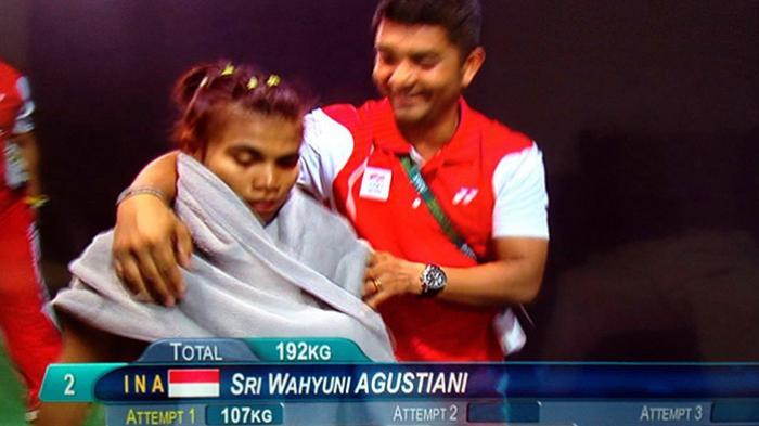 Sri Wahyuni Agustiani, atlet angkat besi wanita Indonesia seusai meraih medali Perak di Olimpiade Rio, Minggu (7/8/2016) diberikan handuk penutup oleh pelatihnya.