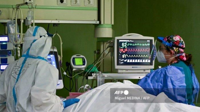 Anggota staf medis yang mengenakan alat pelindung diri (APD) merawat pasien di unit perawatan intensif (ICU) Covid-19 rumah sakit Bolognini di Seriate, Bergamo, pada 12 Maret 2021