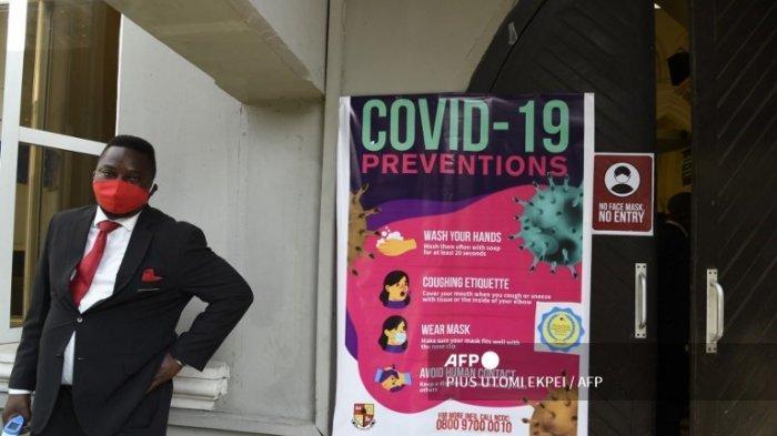 Seorang staf memegang termometer inframerah non-kontak di luar Katedral Gereja Kristus di Lagos, menyusul pembukaan kembali Gereja-Gereja dan pencabutan larangan pertemuan keagamaan oleh pemerintah sebagai tindakan pencegahan untuk memeriksa penyebaran COVID-19 , pada 9 Agustus 2020. .