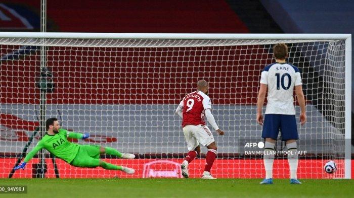Striker Arsenal Prancis Alexandre Lacazette menembak dari titik penalti untuk mencetak gol kedua timnya saat kiper Prancis Tottenham Hotspur, Hugo Lloris (kiri) melakukan penyelaman yang salah selama pertandingan sepak bola Liga Premier Inggris antara Arsenal dan Tottenham Hotspur di Emirates Stadium di London pada Maret. 14, 2021.