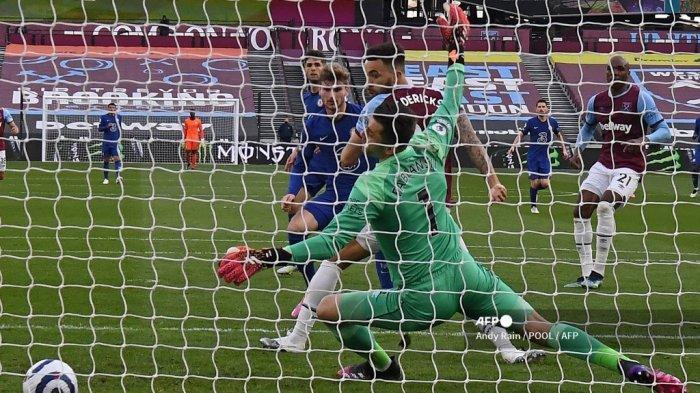 Striker Chelsea Jerman Timo Werner (tengah) menembak melewati kiper Polandia West Ham United Lukasz Fabianski untuk mencetak gol pembuka pertandingan sepak bola Liga Premier Inggris antara West Ham United dan Chelsea di Stadion London, di London timur pada 24 April 2021.