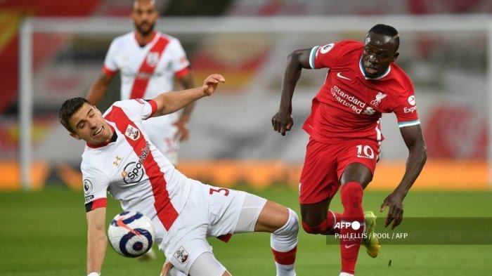 Striker Liverpool Senegal Sadio Mane (kanan) bersaing dengan bek Southampton asal Polandia Jan Bednarek (kiri) selama pertandingan sepak bola Liga Utama Inggris antara Liverpool dan Southampton di Anfield di Liverpool, barat laut Inggris pada 8 Mei 2021.