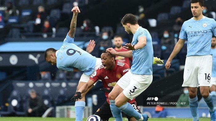 Striker Manchester United Prancis Anthony Martial (tengah) dilanggar di area hukuman oleh striker Manchester City Brasil Gabriel Jesus (kiri) selama pertandingan sepak bola Liga Utama Inggris antara Manchester City dan Manchester United di Stadion Etihad di Manchester, barat laut Inggris, pada 7 Maret 2021.