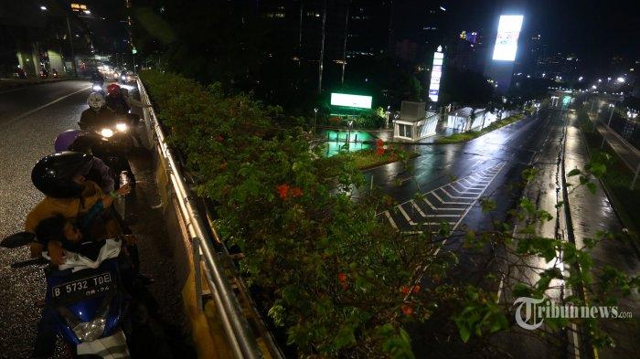 Warga mengamati suasana jalan yang sepi saat diberlakukannya Car Free Night (malam bebas kendaraan) dan Crowd Free Night (malam bebas keramaian) pada malam pergantian tahun di Jalan Jenderal Sudirman, Jakarta, Kamis (31/12/2020). Polda Metro Jaya melakukan Car Free Night dan Crowd Free Night dengan menutup sepanjang Jalan Sudirman-MH Thamrin, Jakarta pada malam pergantian tahun untuk mencegah kerumunan warga. TRIBUNNEWS/IRWAN RISMAWAN