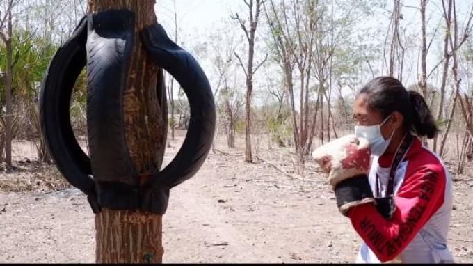 Susanti Ndapataka, atlet NTT Peraih Emas di ajang PON XX Papua berlatih menggunakan ban bekas yang dipasang di batang pohon.