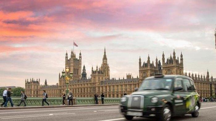 Taksi khas London melintas di depan gedung parlemen Inggris.