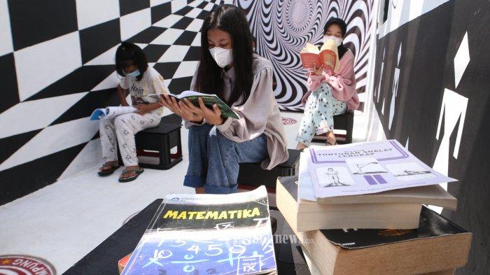 Sejumlah anak-anak membaca buku pelajaran dan pengetahuan di Taman Baca Oase, Gang Sedap Malam, Kupang Teba, Telukbetung Utara, Jumat (21/5/2021).  Taman  baca oase merupakan bak penampungan sanitasi atau septic tank yang dihiasi lampu, lukisan mural dan  tempat berkumpul anak-anak serta menjadi spot foto. Sementara itu, taman baca oase ini dikelola secara swadaya oleh warga untuk menarik minat baca anak-anak sekitar. (Tribunlampung.co.id/Deni Saputra)