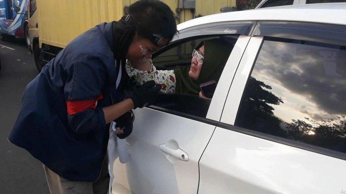 Fitri, seorang penumpang di dalam mobil yang terjebak macet memberikan semangat ke arah mahasiswa pada Senin (30/9/2019).