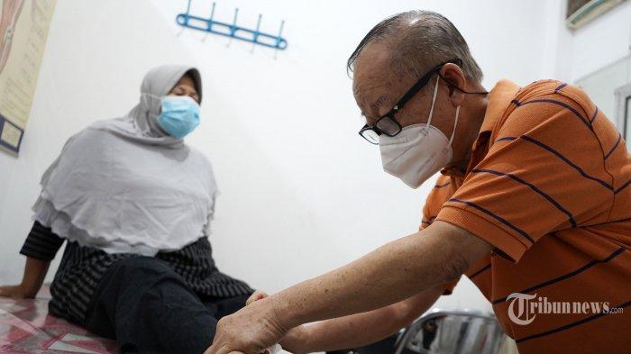 Mulyadi Wong atau Ko Amuk (75) melakukan terapi tusuk jarum kepada pasiennya di kediamannya di Jakarta, Jumat (26/2/2021). Tribunnews/Irwan Rismawan