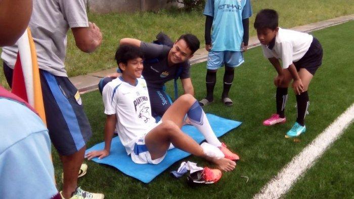 CEDERA: Pemain muda Persib Bandung Ahmad Baasith (kiri) didampingin Fisioterapi Benidektus Adi Prianto menjalani terapi pada engkel kaki kanan di Lapangan Sepakbola Lodaya, Bandung, Selasa (21/2). Baasith cedera saat mengikuti latihan beberapa waktu lalu.(TRIBUN JABAR/DENI DENASWARA)