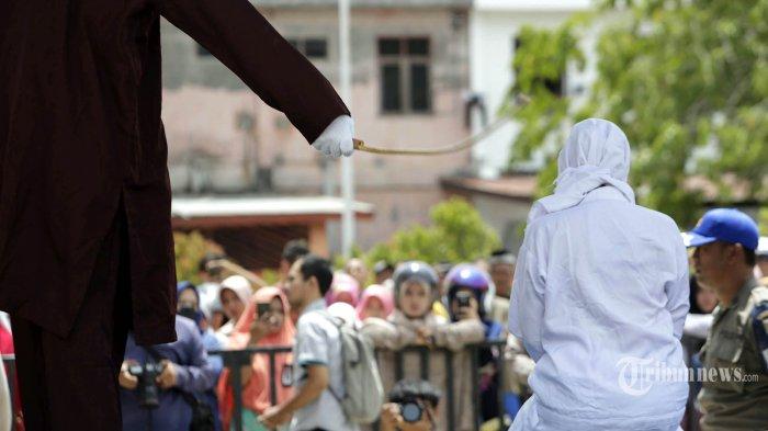 Algojo melakukan eksekusi hukuman cambuk terhadap terpidana pelanggar hukum syariat Islam di halaman Masjid Baitushalihin, Ulee Kareng, Banda Aceh, Kamis (1/8/2019). Sebanyak 11 orang dihukum cambuk di muka umum karena melanggar pasal 23 dan 25 Qanun Nomor 6 Tahun 2014 tentang hukum jinayat. Serambi Indonesia/Budi Fatria
