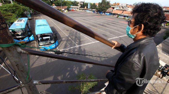 Warga melihat dari jembatan penyeberangan orang (JPO) suasana sepi dari penumpang dan bus di Terminal Cicaheum, Kota Bandung, Jawa Barat, Rabu (13/5/2020). Sejak pandemi virus corona (Covid-19) dan adanya larangan mudik Lebaran, pengguna bus terus menurun, sehingga pengelola layanan bus menghentikan operasi untuk sementara. Tribun Jabar/Gani Kurniawan