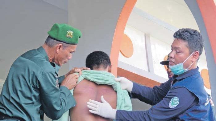 Petugas medis memeriksa punggung terpidana kasus masir (judi) yang lebam-lebam berwarna merah bekas cambukan saat menjalani ekseskusi cambuk di Alun-alun Suka Makmue, Nagan Raya, Jumat (13/3/2020).