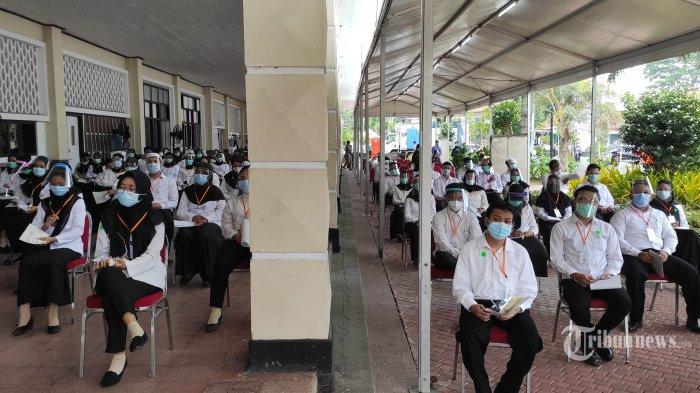 Peserta seleksi kompetisi bidang (SKB) bagi CPNS Pemkot Surabaya saat akan mengikuti tes di GOR Pancasila, Kota Surabaya, Jawa Timur, Selasa (22/9/2020). Seleksi itu menerapkan protokol kesehatan Covid-19 secara ketat, mulai dari mengenakan masker, pelindung wajah, dan sarung tangan serta jarak antar peserta tes, termasuk memisahkan peserta dengan hasil rapid tes reaktif dalam bilik khusus. Sebanyak 1.142 orang mengikuti SKB CPNS Pemkot Surabaya selama 3 hari di mana dalam satu hari terdapat 3 sesi dengan peserta sebanyak 140 orang. Surya/Ahmad Zaimul Haq