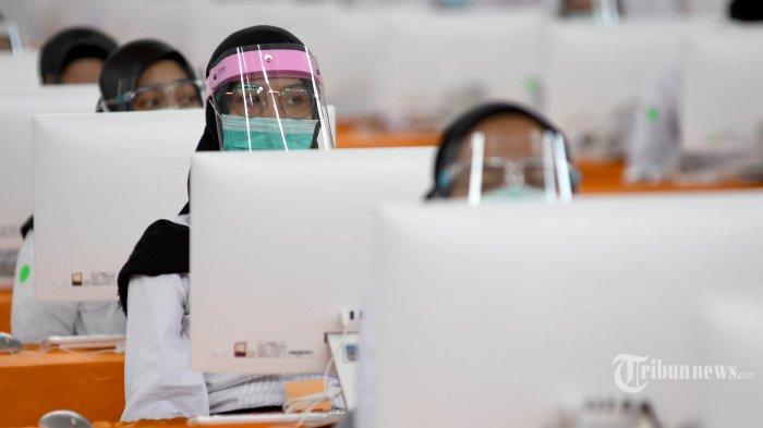 Peserta seleksi kompetisi bidang (SKB) bagi CPNS Pemkot Surabaya bersiap mengikuti tes di GOR Pancasila, Kota Surabaya, Jawa Timur, Selasa (22/9/2020). Seleksi itu menerapkan protokol kesehatan Covid-19 secara ketat, mulai dari mengenakan masker, pelindung wajah, dan sarung tangan serta jarak antar peserta tes, termasuk memisahkan peserta dengan hasil rapid tes reaktif dalam bilik khusus. Sebanyak 1.142 orang mengikuti SKB CPNS Pemkot Surabaya selama 3 hari di mana dalam satu hari terdapat 3 sesi dengan peserta sebanyak 140 orang. Surya/Ahmad Zaimul Haq