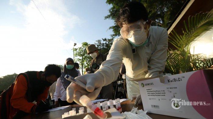 Petugas medis menunjukan alat swab pada kegiatan tes swab kepada penumpang KRL di Stasiun Bekasi, Jawa Barat, Selasa (5/5/2020). Tes swab yang dilakukan secara random untuk 300 penumpang dengan mengumpulkan cairan dari bagian belakang hidung dan tenggorokan tersebut sebagai salah satu metode untuk mendeteksi dan mencegah penyebaran virus corona (Covid-19) di transportasi umum. Tribunnews/Jeprima